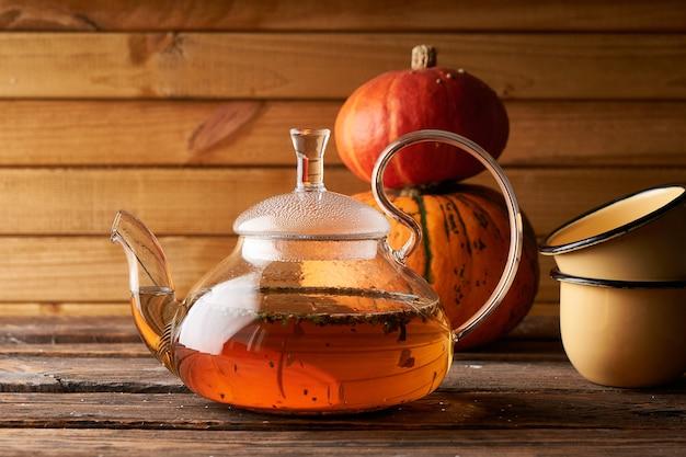 Tetera con té caliente elaborado, calabaza fnd cookies sobre un fondo de madera, acogedor espacio de copia