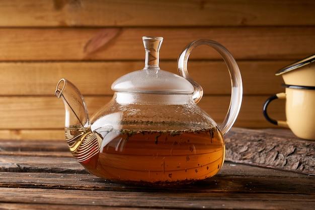 Tetera con té caliente elaborado sobre un fondo acogedor de madera, espacio de copia