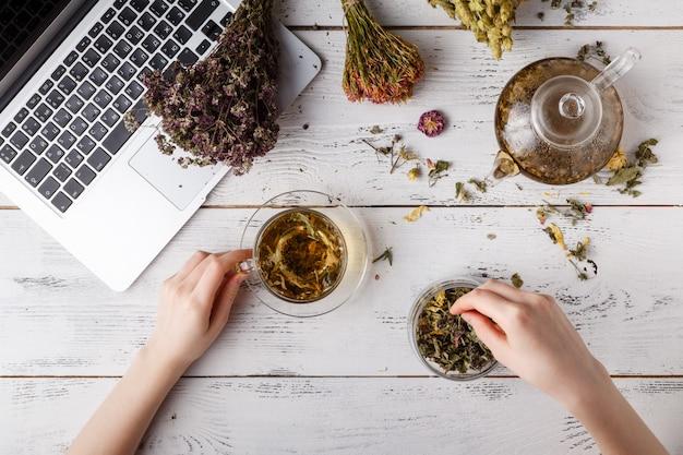 Tetera con té de hierbas en la mesa de la cocina y mujer escribir receta