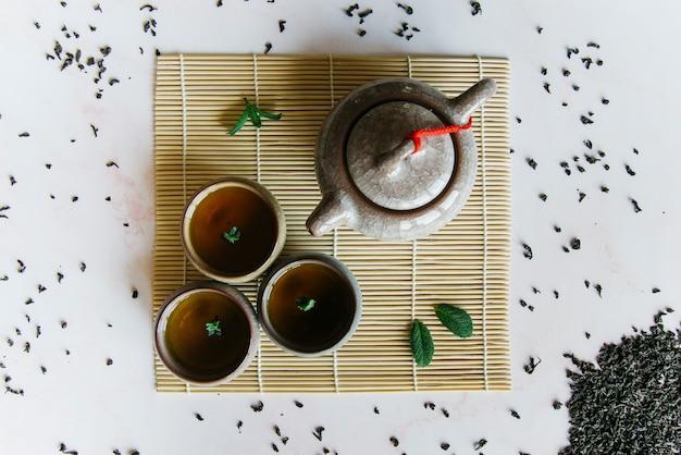 Tetera tradicional china o japonesa; taza de té en mantel individual
