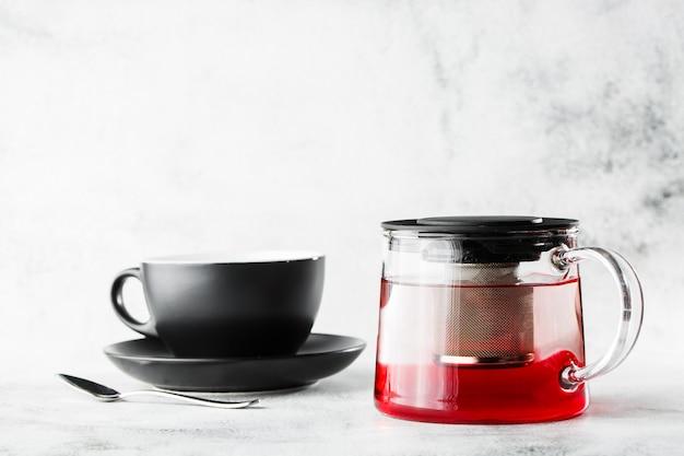 Tetera de vidrio con taza oscura de té rojo, frutas o bayas aislado sobre fondo de mármol brillante. vista aérea, copia espacio. publicidad para el menú del café. menú de cafetería. foto horizontal