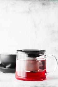 Tetera de vidrio con taza oscura de té rojo, frutas o bayas aislado sobre fondo de mármol brillante. vista aérea, copia espacio. publicidad para el menú del café. menú de cafetería. foto vertical.