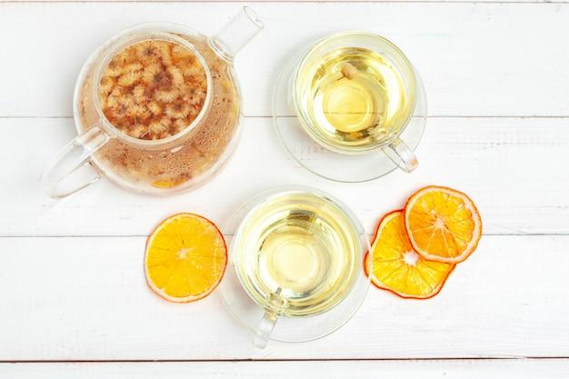 Tetera de vidrio y una taza de té de hierbas en madera blanca