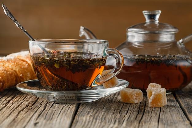 Tetera de vidrio y taza con té de hierbas en la mesa de madera vieja
