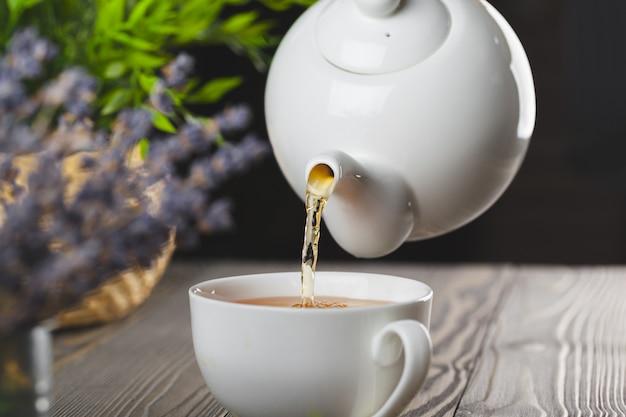 Tetera de vidrio con una taza de té negro en la mesa de madera