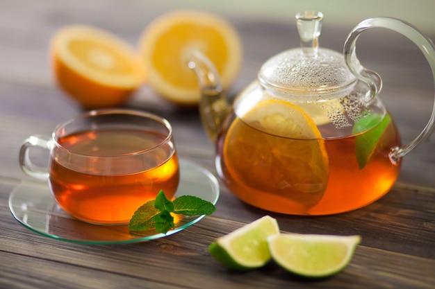 Tetera de vidrio y una taza de té negro con naranja, limón, menta limón en una mesa de madera