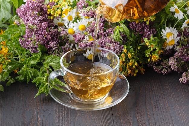Tetera de vidrio y taza con té verde en la mesa de madera vieja con hierbas frescas
