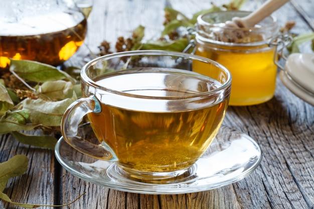 Tetera de vidrio y taza con té verde en la mesa de madera vieja.