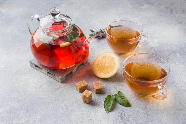 Tetera de vidrio con té, menta y limón en mesa gris con espacio de copia