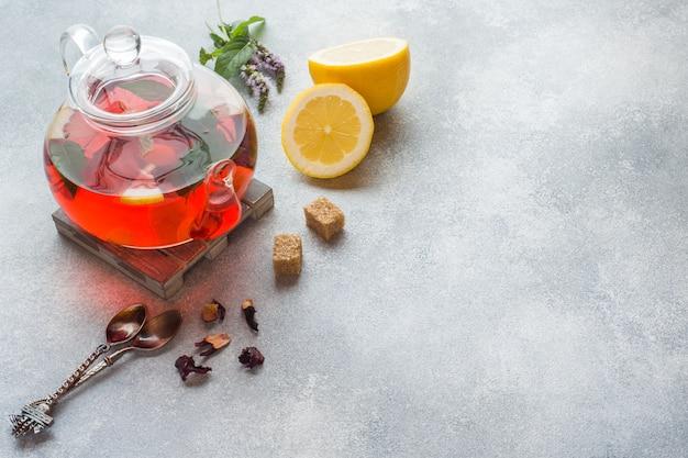 Tetera de vidrio con té, menta y limón en mesa gris con espacio de copia.