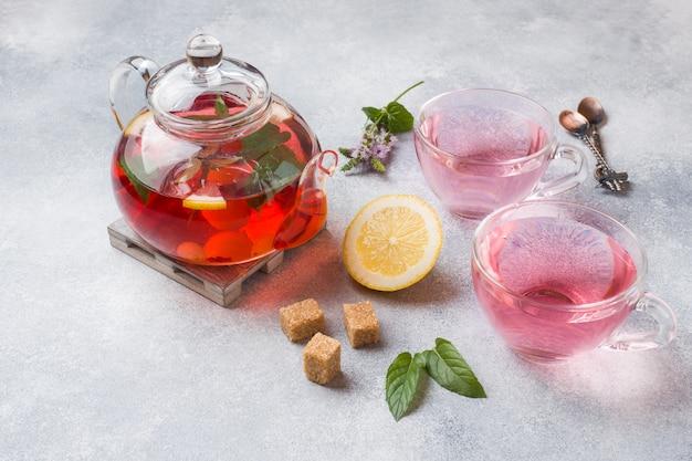 Tetera de vidrio con té, menta y limón sobre la mesa gris