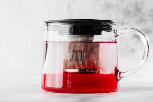 Tetera de vidrio de té rojo, fruta o bayas aislado sobre fondo de mármol brillante. vista aérea, copia espacio. publicidad para el menú del café. menú de cafetería. foto horizontal