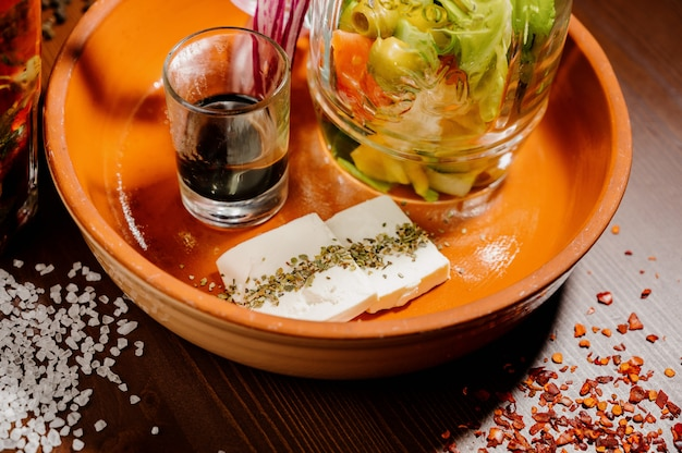 Una tetera de vidrio con té y una taza de vidrio con soporte de té sobre la mesa