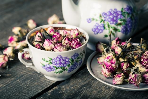 Tetera vintage y taza con flores de té en flor