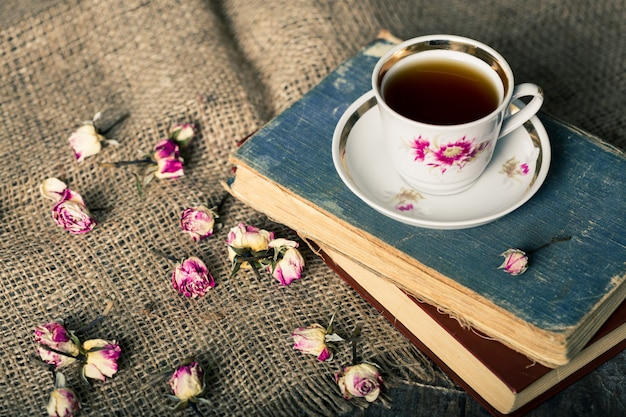 Tetera vintage y taza con flores de té florecientes