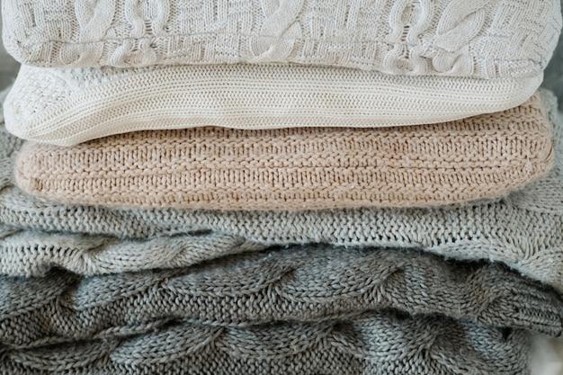 Textiles para el hogar de invierno. una manta de punto cálida y acogedora y una pila de almohadas suaves.