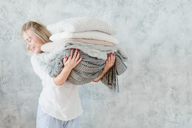 Textiles para el hogar de temporada fría. mujer sonriente con manta tejida y pila de almohadas.