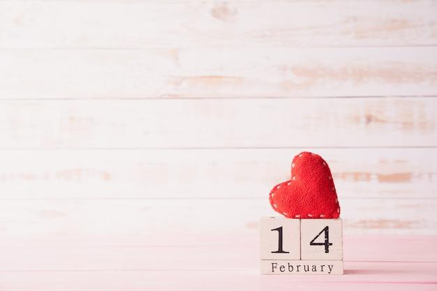 Texto del 14 de febrero en el bloque de madera con corazón rojo sobre fondo de madera.