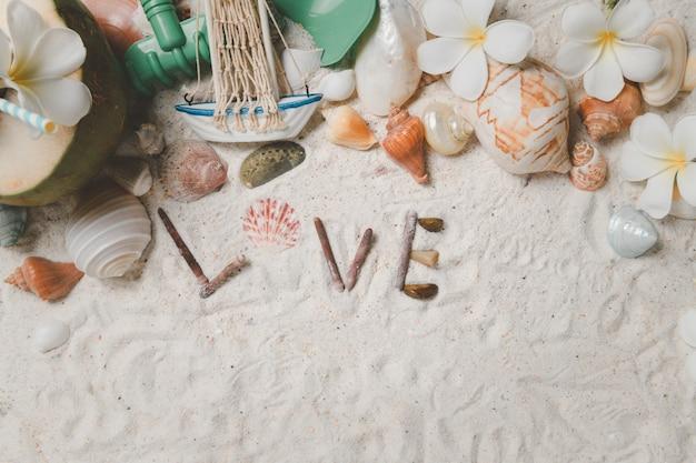 Texto de amor con conchas y flores de plumeria sobre fondo de arena