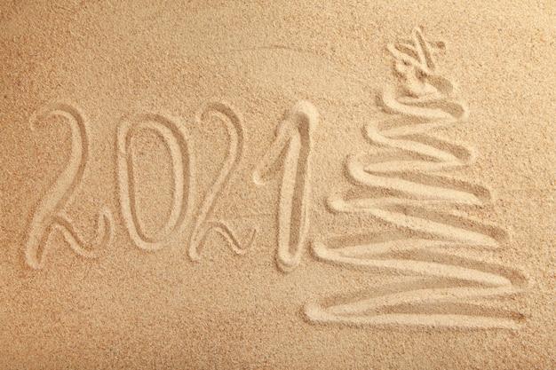 Texto de año nuevo 2021 con árbol de navidad sobre fondo de arena