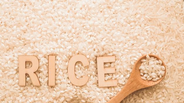 Texto de arroz sobre los granos de arroz blanco con cuchara de madera