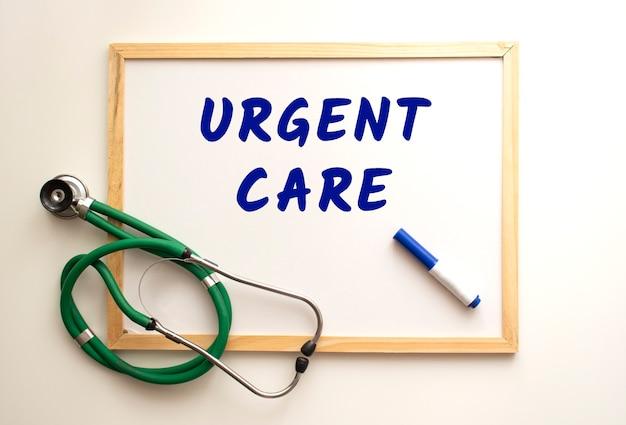 El texto atención urgente está escrito en un tablero de oficina blanco. cerca hay un estetoscopio.