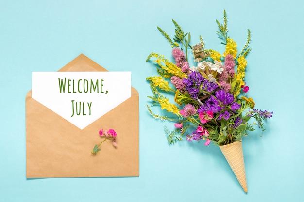 Texto de bienvenida de julio en una tarjeta de papel en un sobre artesanal y un ramo de flores de colores en un cono de helado de waffle en azul