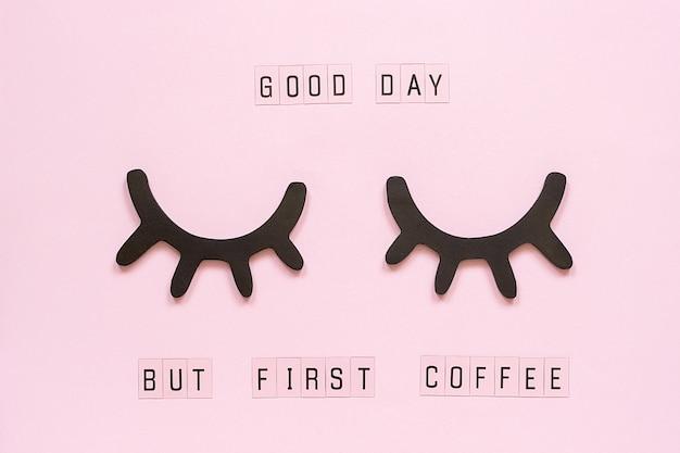 Texto buenos días, pero primero café y pestañas negras decorativas de madera, ojos cerrados, en papel rosa pastel