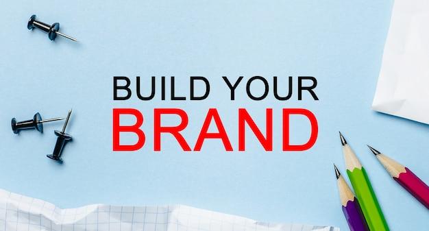 Texto build your brand en un bloc de notas blanco con lápices sobre un fondo azul. concepto de negocio