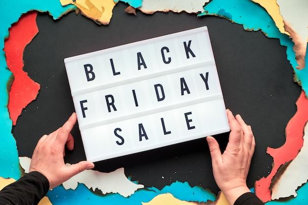 Texto de caja de luz venta de viernes negro con manos en papel quemado