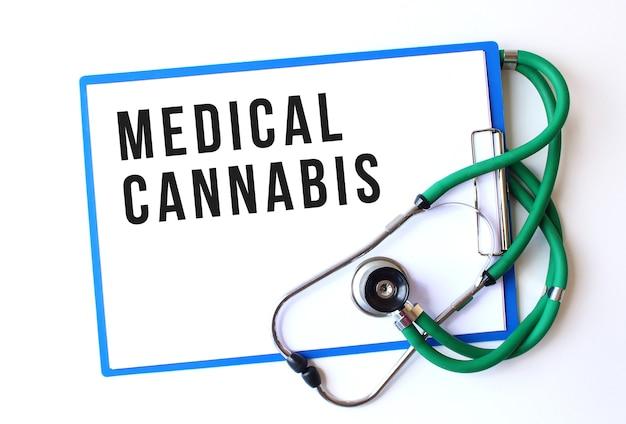 Texto de cannabis médico en carpeta médica con documentos y estetoscopio sobre fondo blanco. concepto médico.