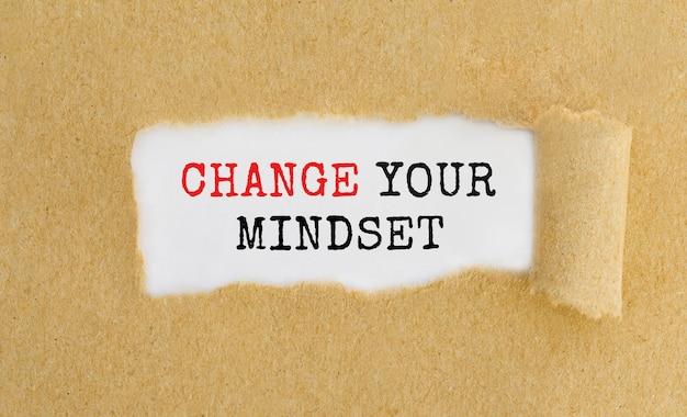 Texto change your mindset que aparece detrás de papel marrón rasgado.