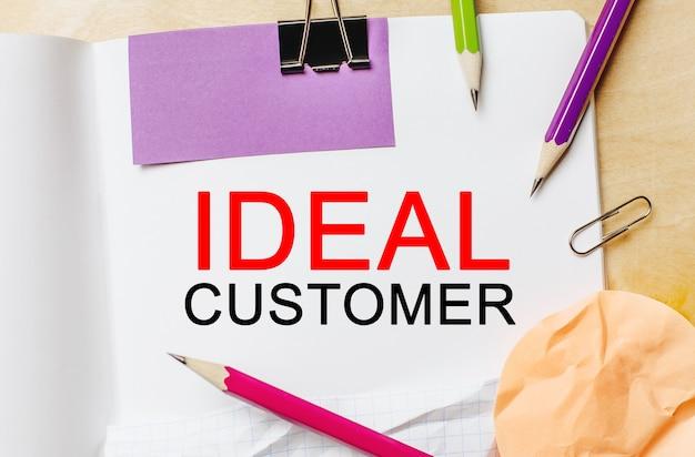 Texto cliente ideal sobre un fondo de nota blanco con lápices, pegatinas y clips. concepto de negocio