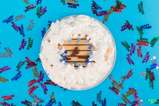 Texto colorido de feliz cumpleaños alrededor de la torta con velas encendidas sobre fondo azul