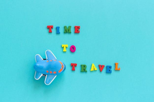 Texto colorido tiempo para viajar y avión de juguete divertido para niños sobre fondo de papel azul, postal de turismo,