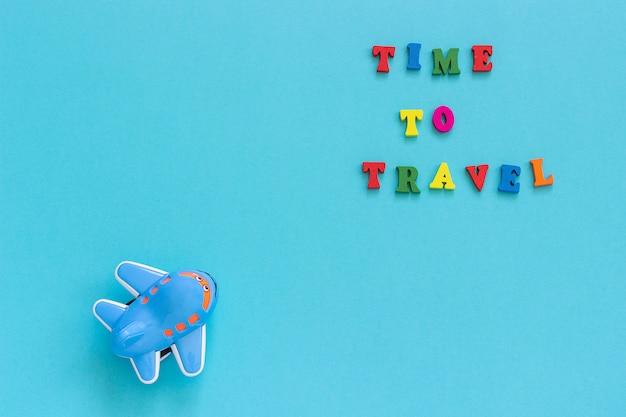 Texto colorido tiempo para viajar y avión de juguete divertido para niños sobre fondo de papel azul.