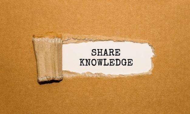 El texto compartir conocimientos que aparece detrás de un papel marrón rasgado