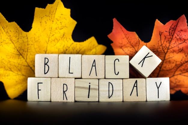 Texto de concepto de venta y viernes negro con venta de descuento de otoño, oferta de temporada sobre fondo negro con coloridas hojas de otoño closeup