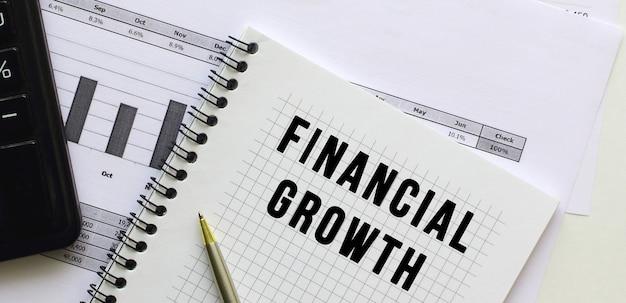 Texto crecimiento financiero en la página de un bloc de notas sobre gráficos financieros en el escritorio de la oficina