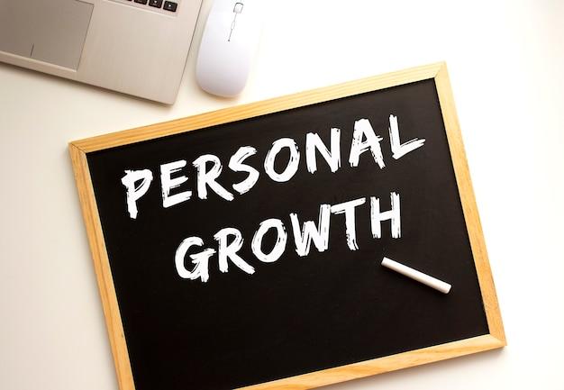 Texto crecimiento personal escrito con tiza en una pizarra. escritorio de oficina. concepto de negocio.