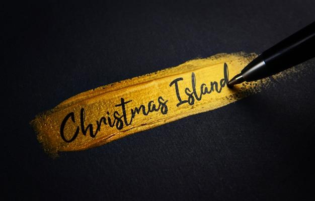 Texto de escritura a mano en la isla de navidad sobre el pincel de pintura dorada