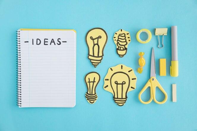 Texto de ideas en un cuaderno espiral; bombillas y efectos de escritorio en fondo azul