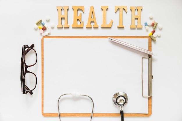 Texto de salud con pastillas sobre el portapapeles con papel; los anteojos; pluma y estetoscopio