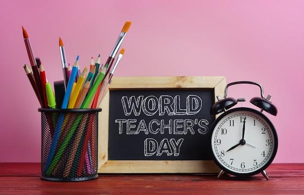 Texto del día mundial del maestro. pizarra, reloj despertador y papelería escolar en basket on pink