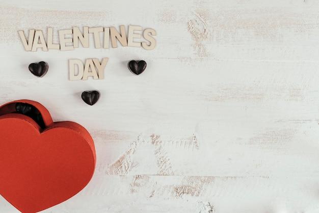Texto del día de san valentín con una caja de corazón llena de chocolates.