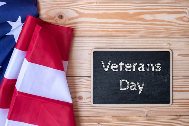 Texto del día de los veteranos escrito en la pizarra con la bandera de los estados unidos