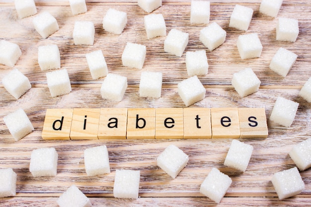Texto de diabetes en terrones de azúcar terrones superficie en escritorio de madera