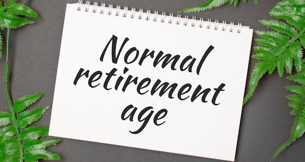 Texto de la edad de jubilación normal con hojas reales de la selva tropical