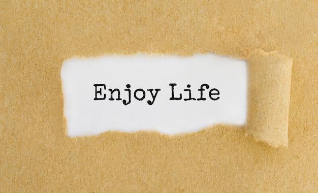 Texto enjoy life que aparece detrás de papel marrón rasgado.