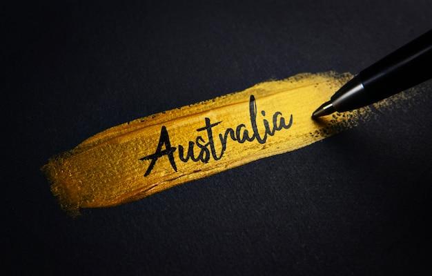Texto de la escritura de australia sobre el pincel de pintura dorada